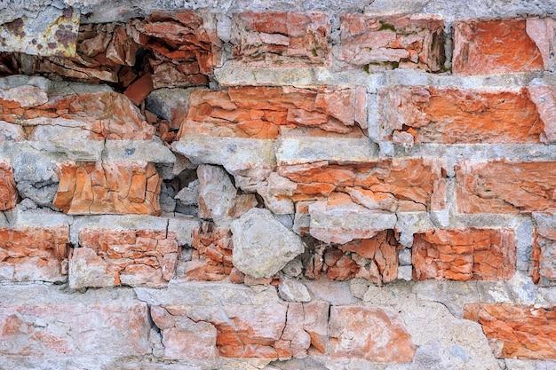Zniszczony mur z cegły, tło.