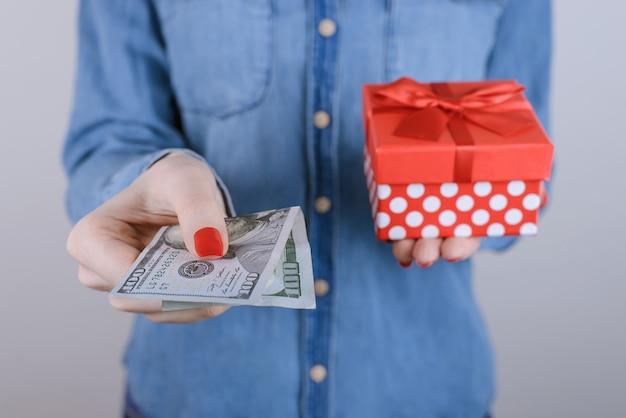 Zniżka sprzedaż wygrać trzymać egoistyczny konsumpcjonizm ludzie osoba moda uroda przyjaciel czerwony koncepcja. przycięte zdjęcie z bliska portret podekscytowanej zadowolonej pani kupującej prezent na białym tle na szarym tle