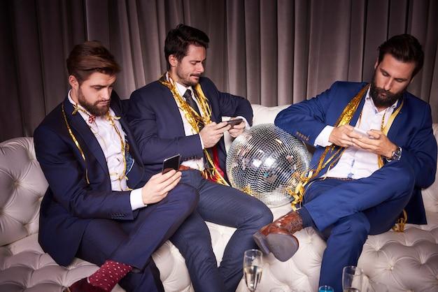 Znudzeni przyjaciele korzystający z telefonu komórkowego na imprezie