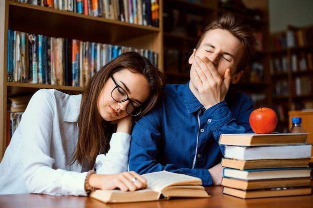 Znudzeni uczniowie zmęczeni ciągłym studiowaniem zasnęli podczas pracy nad projektem przez cały dzień
