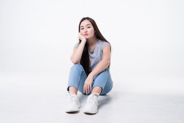 Znudzona azjatycka kobieta siedzi na podłodze na białym tle na białej ścianie.