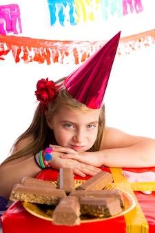 Znudzona blond dziewczyna dzieciak w imprezie z czekoladkami