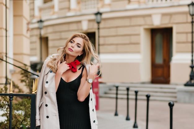 Znudzona dama z blond lokami odwracająca wzrok, spacerująca samotnie po ulicy rano