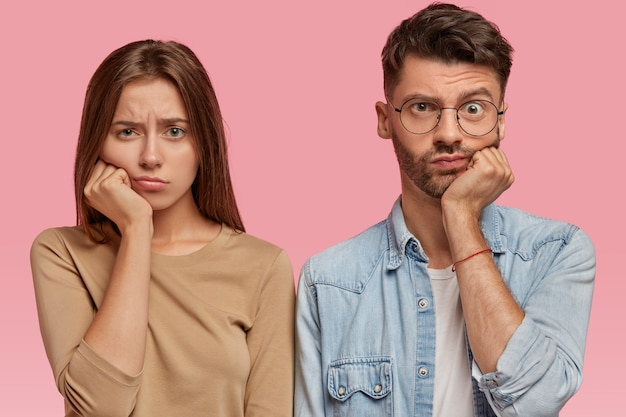 Znudzona dziewczyna i chłopak trzymają dłoń pod brodą, patrzą wprost ze smutkiem, czują się niezadowoleni, długo czekają na coś, stoją pod różową ścianą. koncepcja ludzi i mimiki