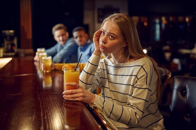 Znudzona dziewczyna pije koktajl przy ladzie w barze. grupa ludzi odpoczywa w pubie, nocny styl życia, kobieta w nocnym klubie