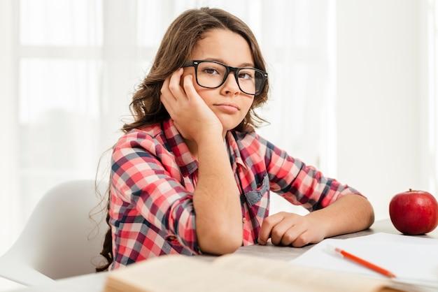 Znudzona dziewczyna pod dużym kątem podczas nauki