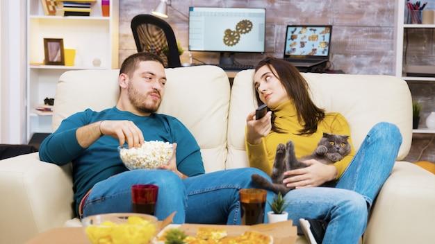 Znudzona dziewczyna siedzi na kanapie z kotem na kolanach, a chłopak obok niej używa pilota do telewizora.
