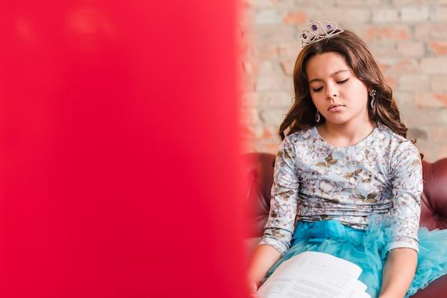 Znudzona dziewczyna siedzi na kanapie ze skryptami