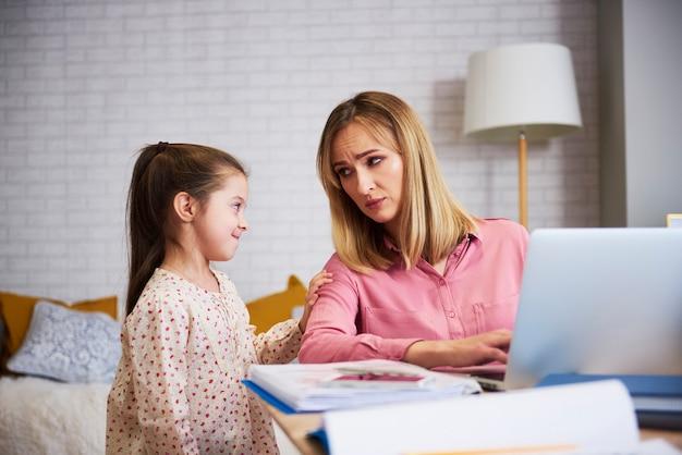 Znudzona dziewczyna z ciężko pracującą młodą mamusią w domowym biurze