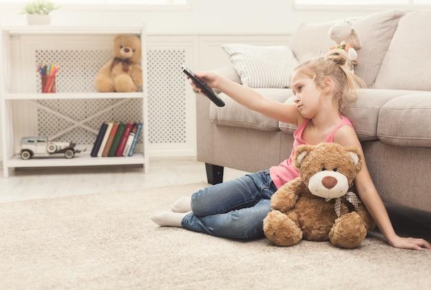 Znudzona dziewczynka ogląda telewizję w domu. dziewczynka siedzi na dywanie podłogowym z pluszowym misiem, trzymając pilota i przełączający kanały, nic ciekawego do zobaczenia, kopia przestrzeń