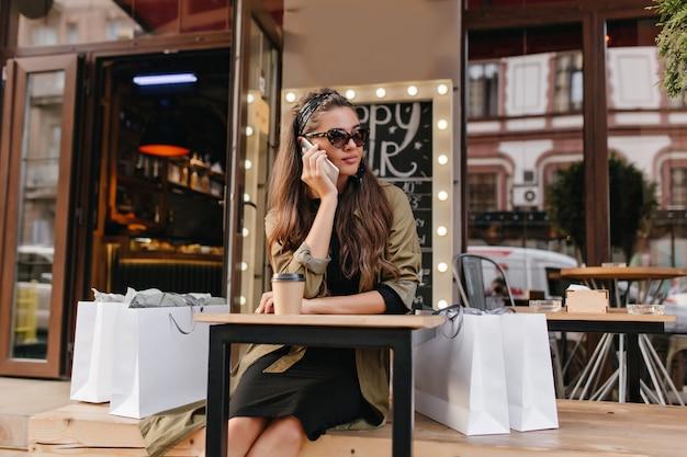 Znudzona kobieta dzwoni do kogoś siedząc w kawiarni na świeżym powietrzu po zakupach
