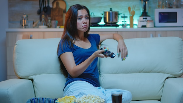 Znudzona kobieta odpoczywa przed telewizorem w salonie, siedząc na kanapie. zmęczona pracą, sama w domu późno w nocy pani relaksuje się na kanapie przed telewizorem trzymając pilota wybierającego kanał z filmem