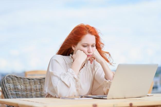 Znudzona kobieta siedzi w kawiarni na ulicy i zdalnie pracuje na laptopie