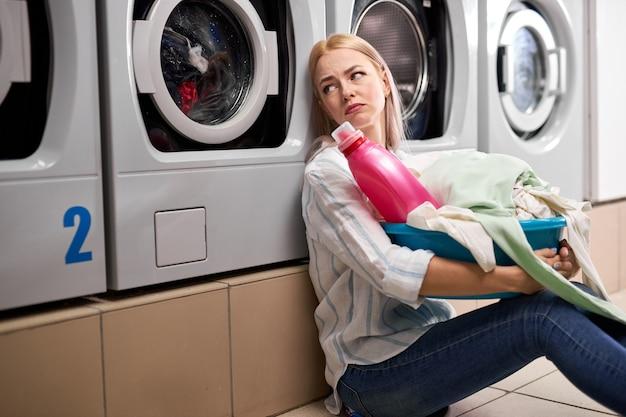 Znudzona kobieta trzymająca brudne ubrania i różową butelkę detergentu w umywalce, siedzi na podłodze oparta o pralkę, siedzi samotnie przygnębiona, w pralni