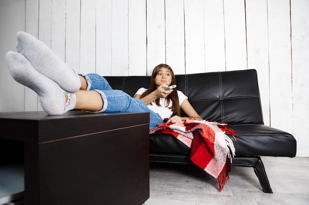 Znudzona ładna kobieta ogląda telewizję, siedząc na kanapie w domu.