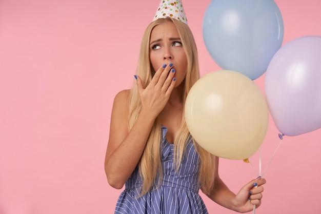 Znudzona ładna młoda kobieta z długimi blond włosami w świątecznych ubraniach i stożkowym kapeluszu, trzymająca balony z helem, pozując na różowym tle, ziewająca i zakrywająca usta uniesioną ręką