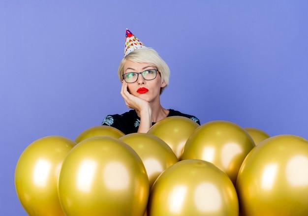 Znudzona młoda blond impreza w okularach i czapce urodzinowej stojącej za balonami, kładąc rękę pod brodą, patrząc na bok na białym tle na fioletowym tle