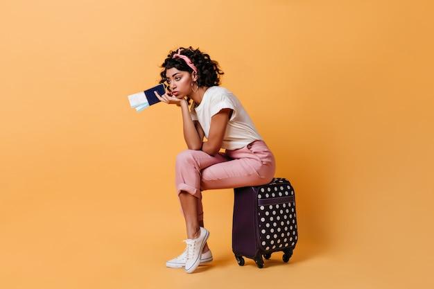 Znudzona młoda kobieta trzyma bilety lotnicze