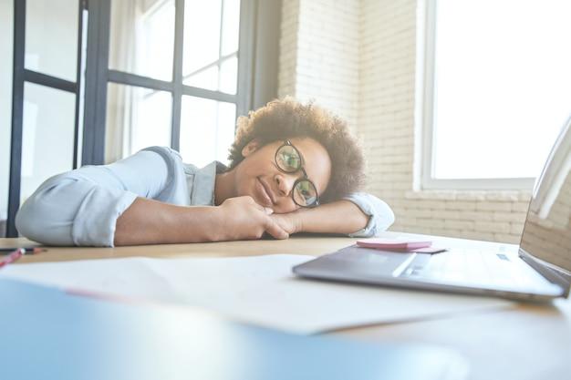 Znudzona nastolatka opiera się na biurku, używając laptopa i ma lekcję online za pośrednictwem aplikacji do czatu wideo, podczas gdy