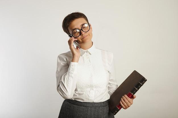 Znudzona nauczycielka z dużą książką zamyka oczy w białej irytacji rozmawiając przez telefon