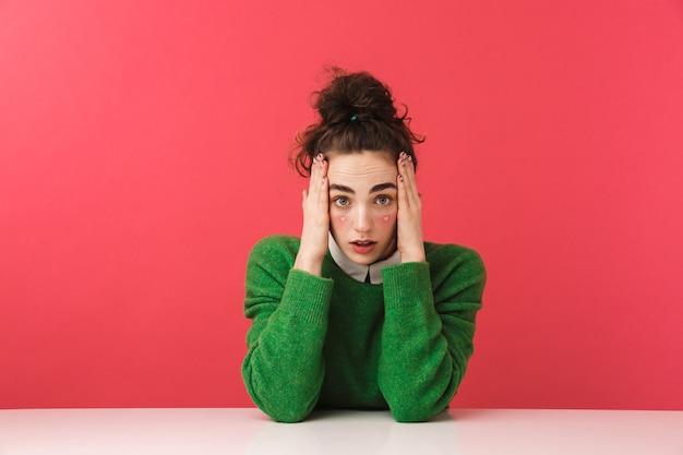 Znudzona piękna dziewczyna młody student siedzi przy stole na białym tle