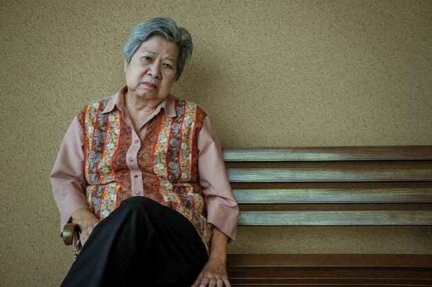 Znudzona przygnębiona starsza kobieta siedzi na ławce.