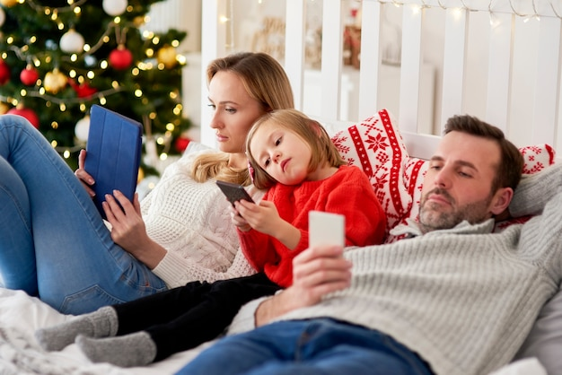 Znudzona rodzina przy użyciu telefonu komórkowego w łóżku na boże narodzenie