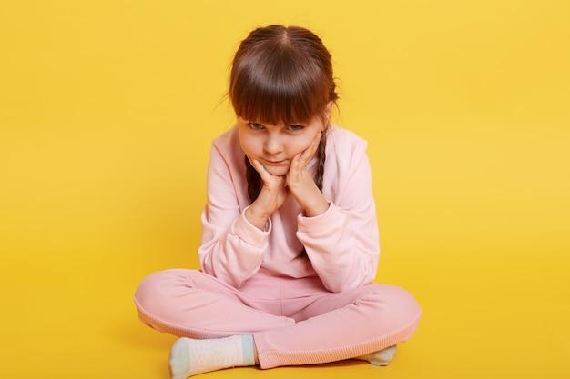 Znudzona śliczna mała europejska dziewczyna siedzi na podłodze i myśli