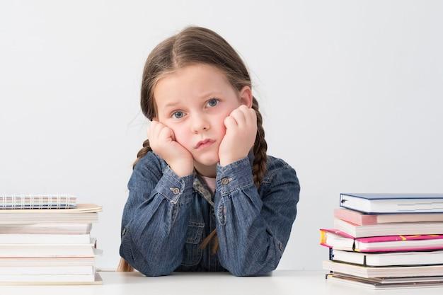 Znudzona uczennica siedzi z głową opartą na rękach, wokół stosy książek.