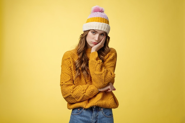 Znudzona zirytowana znużona urocza dziewczyna nie znosi nudnych rozmów pochylająca się dłoń obojętne spojrzenie kamera pod czołem niezainteresowana nieuważna stojąca zaniepokojona żółtym tle