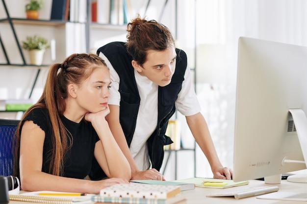 Znudzone, zmęczone nastolatki oglądające zajęcia online lub webinarium na komputerze w domu, nauka w domu z powodu pandemii koronawirusa