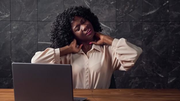 Znudzony afro-sekretarka z kręconymi włosami rozciąga się do tyłu, siedząc przy brązowym drewnianym stole z szarym laptopem przez marmurową ścianę w pustym biurze