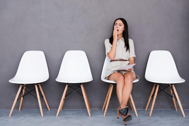 Znudzony czekaniem. znudzona młoda kobieta trzymająca papier i odwracająca wzrok siedząc na krześle na szarym tle