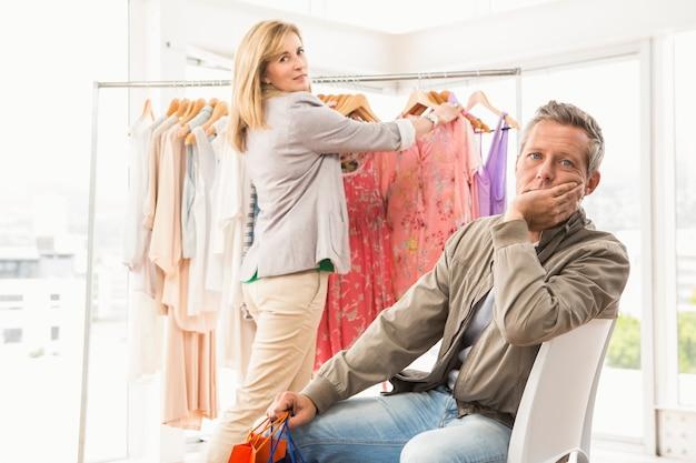 Znudzony człowiek czeka na swoją kobietę zakupy
