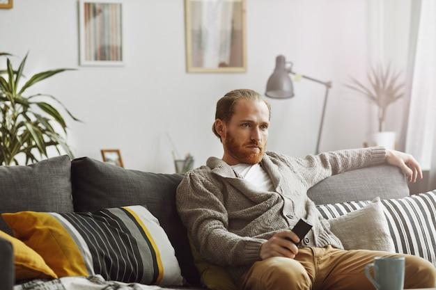 Znudzony człowiek ogląda telewizję w domu