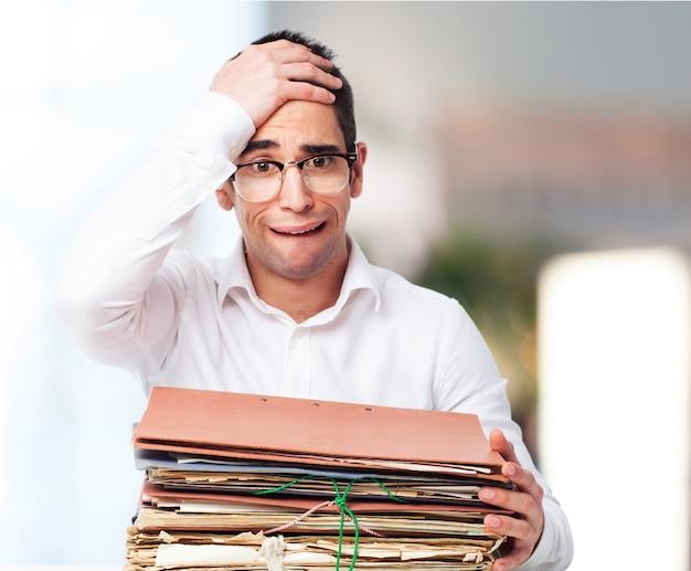 Znudzony człowiek patrząc na stos papierów z jednej strony na czole