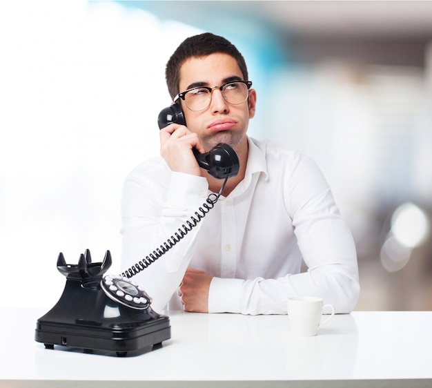 Znudzony człowiek rozmawia na czarnym telefon