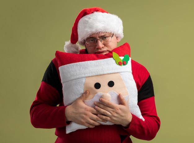 Znudzony dorosły mężczyzna w okularach i czapce świętego mikołaja trzymający poduszkę świętego mikołaja od tyłu odizolowaną na oliwkowozielonej ścianie
