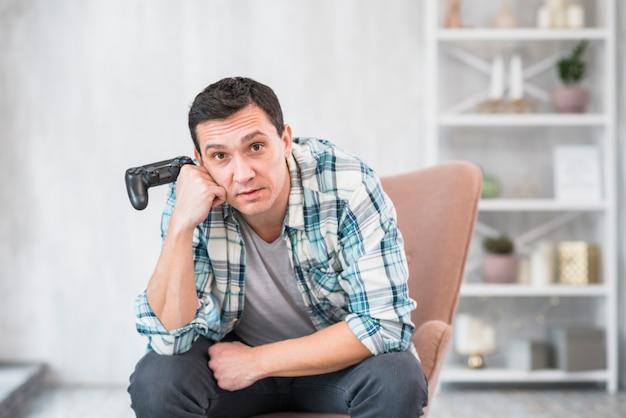 Znudzony facet siedzi w fotelu z gamepad