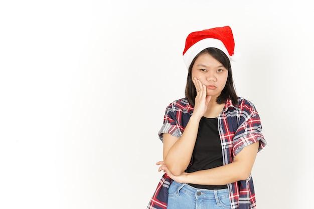 Znudzony i nadąsany wyraz twarzy pięknej azjatyckiej kobiety w czerwonej koszuli w kratę i santa hat