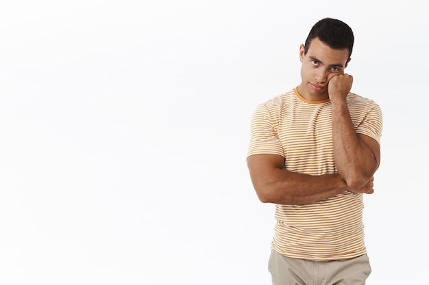 Znudzony i nierozbawiony kaukaski mężczyzna stojący niechętnie na białym tle