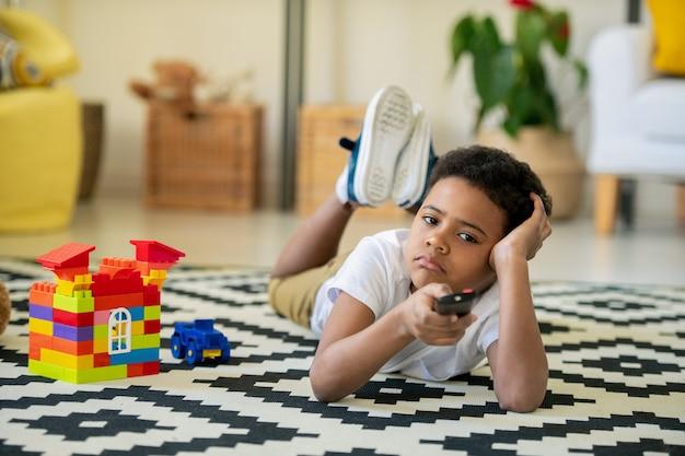 Znudzony i nieszczęśliwy uroczy mały chłopiec pochodzenia afrykańskiego, naciskając przycisk pilota, leżąc przed telewizorem w domu