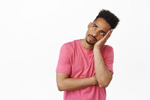 Znudzony i zirytowany afroamerykański student płci męskiej, facet przewraca oczami i wpatruje się w pustą rozstawioną twarz w lewym górnym rogu, uczestniczy w irytującym nudnym spotkaniu na białym