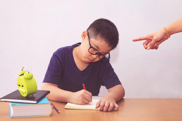 Znudzony i zmęczony chłopiec azjatyckich studentów odrabiania lekcji. gniewna matka wskazuje na niego