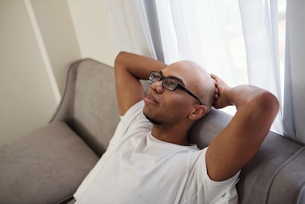 Znudzony lub przygnębiony młody murzyn w okularach siedzi na kanapie i patrząc w sufit