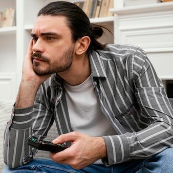 Znudzony mężczyzna próbuje znaleźć coś do oglądania w telewizji