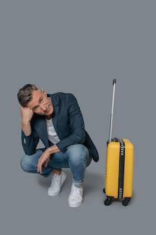 Znudzony mężczyzna w pobliżu walizki czeka na lot