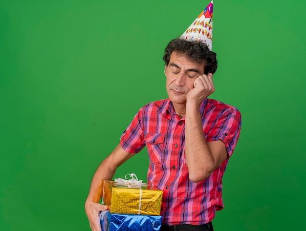 Znudzony mężczyzna w średnim wieku strony w czapce urodzinowej, trzymając paczki z prezentami, kładąc rękę na twarzy z zamkniętymi oczami na białym tle na zielonej ścianie