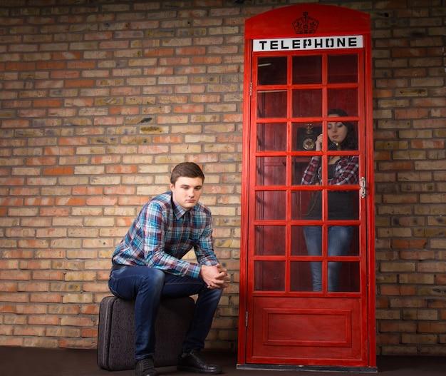 Znudzony młody człowiek czeka, aż jego żona lub dziewczyna skończą rozmawiać przez telefon w czerwonej brytyjskiej budce telefonicznej, siedząc cierpliwie na zewnątrz na swojej walizce