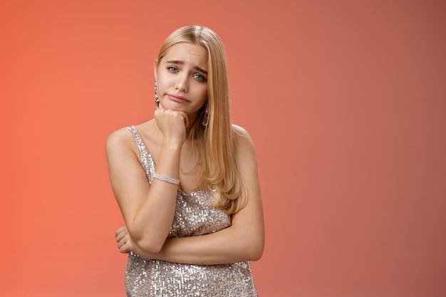 Znudzony niezainteresowany nieostrożny atrakcyjny elegancki młody glamour blond kobieta szczupła głowa uśmiechnięty obojętny czuć nudę niechętnie słyszeć nudną, nieciekawą historię stojącą zirytowany czerwonym tle.